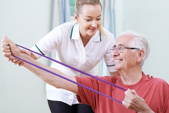 Older man doing rehab exercise with a nurse.