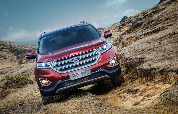 A red Ford Edge with Chinese license plates, on rocky terrain.