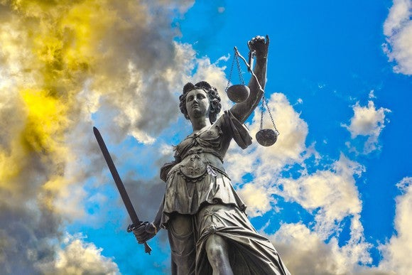A statue of Lady Justice, set against swirling clouds.