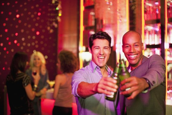 Two men toasting with bottled beers in a club