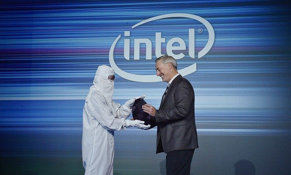 "Outgoing Intel executive Stacy Smith on the right being handed a silicon wafer by an engineer in a ""bunny suit"" on the left."