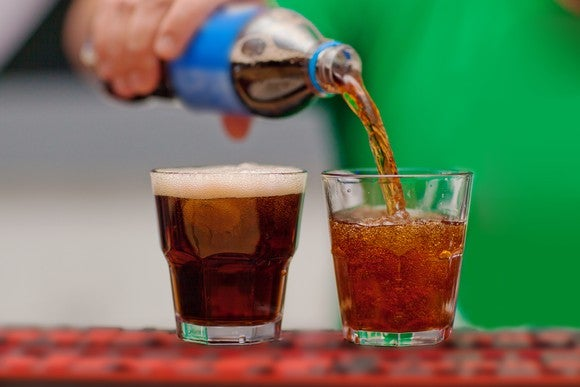 hand pours bottle of brown soda into two glasses.