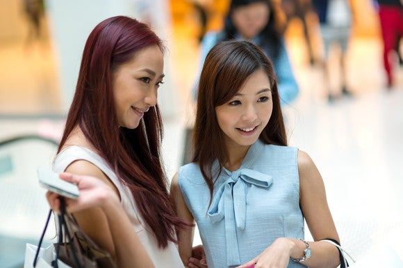 Two women shop at a luxury mall in Hong Kong.