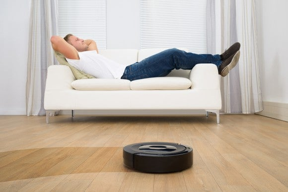 A man reclines on a couch as a robotic vacuum cleans the floor.