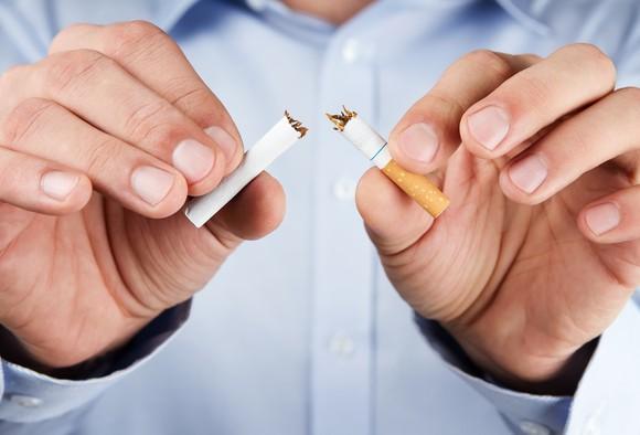 Hands tearing cigarette in half