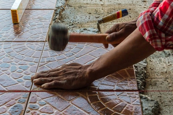 A person using a rubber mallet to install floor tile.
