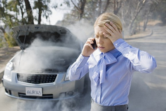 Frustrated-looking woman in front of overheating car.