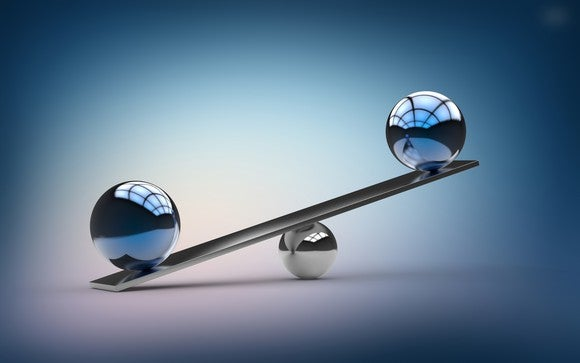 Two polished metal spheres balancing on a seesaw, with one side touching the ground and the other in the air.