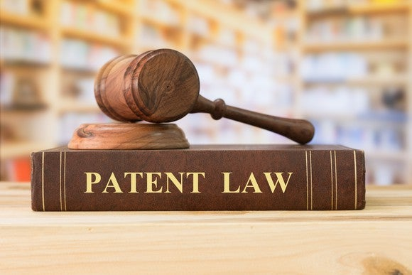 """A gavel sitting on top of a book titled """"Patent Law."""""""