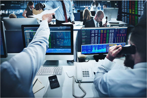 A Wall Street trading desk, with one person trading on the phone and a second person handing over a piece of paper to a third person.
