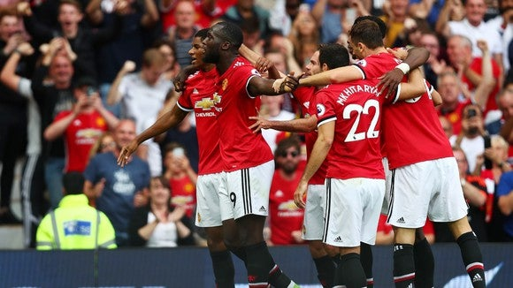 The Manchester United team celebrates on the field after defeating a rival. MU's team wears red jerseys and white shorts.