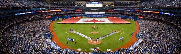 The inside of Rogers Centre, home of the Toronto Blue Jays baseball team. The Canadian flag with the red maple leaf is being displayed across the outfield.