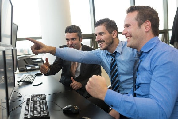 3 men in shirts and ties in an office setting smile as one points to a computer monitor.