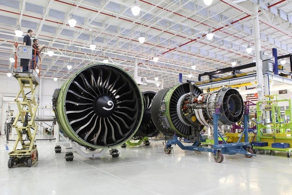 A large factory floor with high ceilings and workers working on three massive aircraft jet engines.