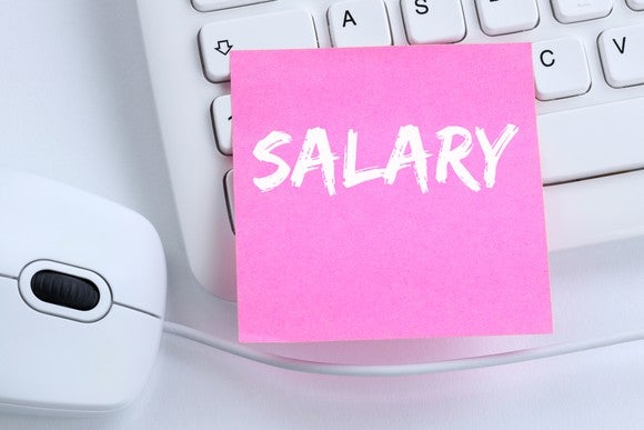 "Pink post-it with the word ""salary"" stuck on a keyboard next to a mouse"