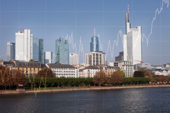 Picture of a city's skyline with a rising stock chart super-imposed in the background.