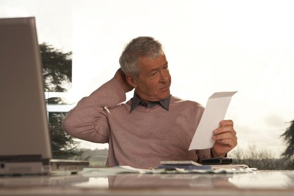 An older male scratching his head while looking at a piece of paper in his hand while sitting behind a desk.