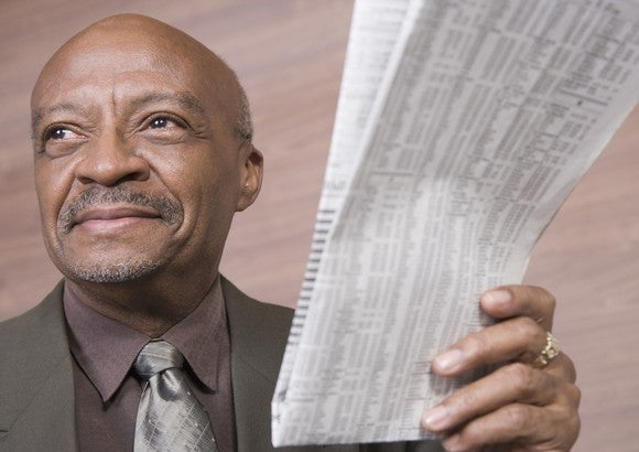 Senior businessman holding up a newspaper with stock listings.