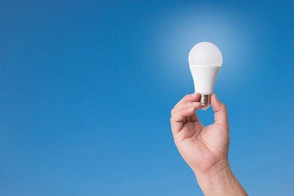 Hand holding an LED lightbulb in front of a blue background