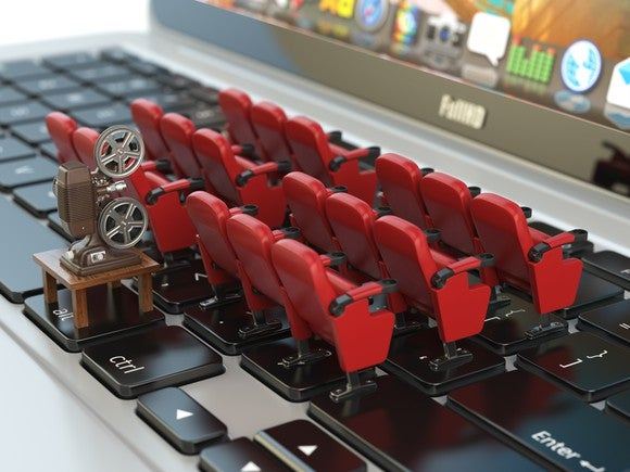 Rows of tiny movie seats placed on a laptop keyboard.