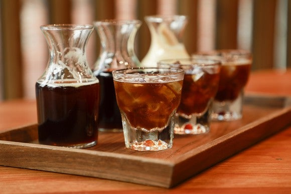 Three decanters and glasses filled with cold-brew coffee