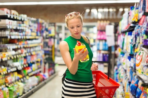 A woman reads the back of a bottle apparently filled with cleaning fluid while shopping inside a store.
