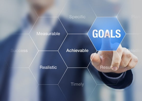 """Man selecting """"goals"""" on a touch screen with buzz words"""