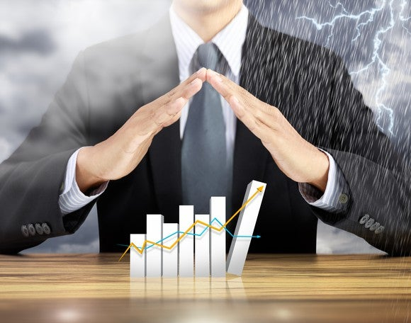 Businessman holding hands over chart in midst of storm