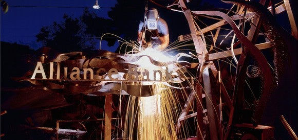 Welder working on a metal apparatus shown with an Alliance Bank logo in front of it.