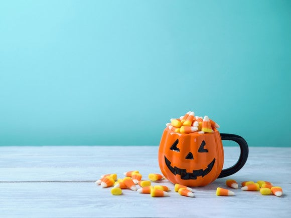 A jack-o-lantern mug is filled with candy corn.