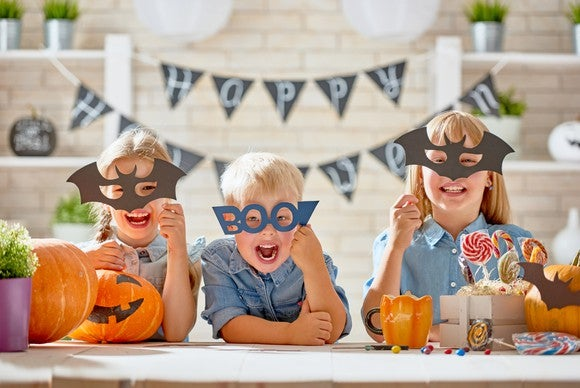 "Kids pose with masks in front of a ""happy Halloween"" sign."