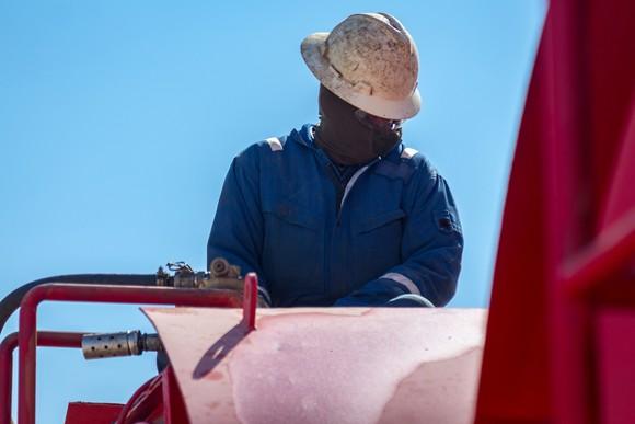 Oil-rig worker at pump.
