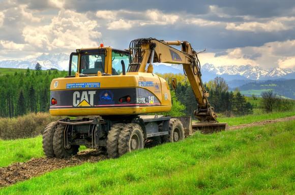 a caterpillar excavator going through a field