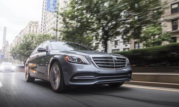 A silver 2018 Mercedes-Benz S450, a big four-door luxury sedan, on a city street.