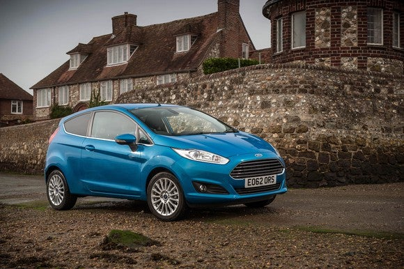 A teal Ford Fiesta two-door hatchback in front of a stone building in Europe.