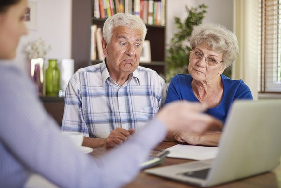 Senior man looking shocked and senior woman looking concerned as material is presented on a laptop by a third party