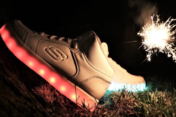 A pair of Skechers shoes in the dark with lighted soles and a sparkler lighting the background.