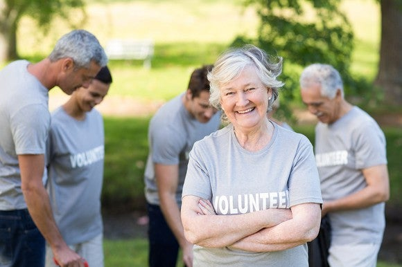 """Older woman with """"volunteer"""" on her shirt smiles at the camera."""