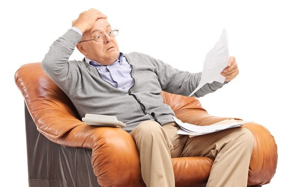 Older man looks at a bill with a surprised look on his face.