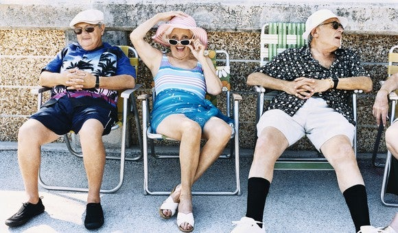 A group of retirees smiling and chatting in folding beach chairs.