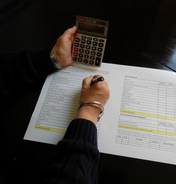 Hands holding a calculator and completing a form