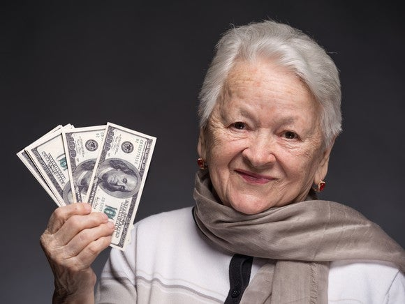 A senior woman holding a small stack of hundred dollar bills in her right hand.