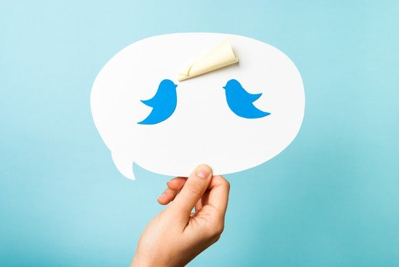 Two Twitter bird icons in a speech bubble, with a rolled-up sticky note forming a megaphone for one