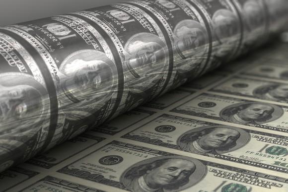 U.S. hundred-dollar bills roll through a printing press.