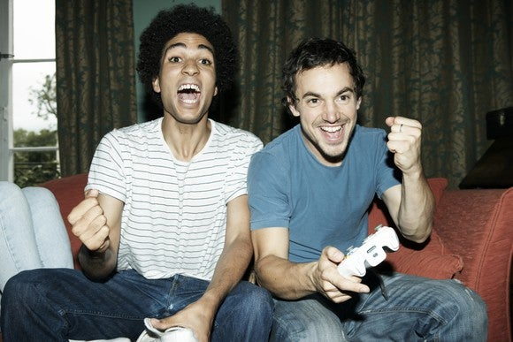 Two young men celebrate while holding video game controllers.