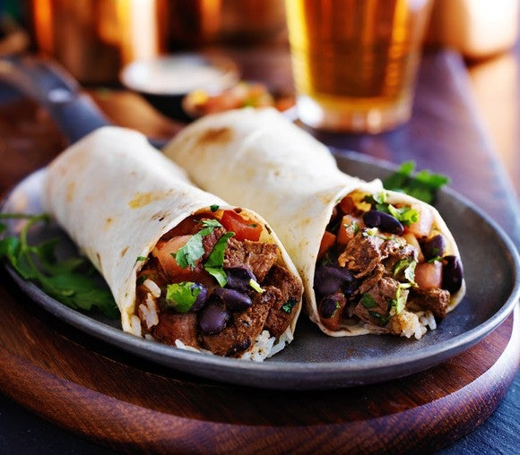 Two burritos served in a skillet, sitting on a tabletop with glasses of drinks in the background.