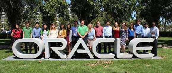 Group of employees posting behind an Oracle sculpture outside headquarters.