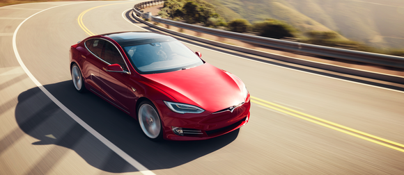 A red Tesla Model S on a scenic road.