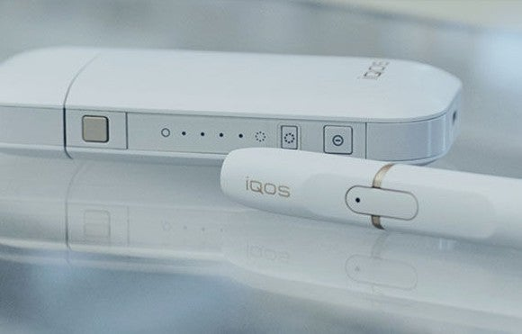 Philip Morris IQOS system, pictured in white, consists of a holder, charger, and a heat stick used to inhale the vapor.