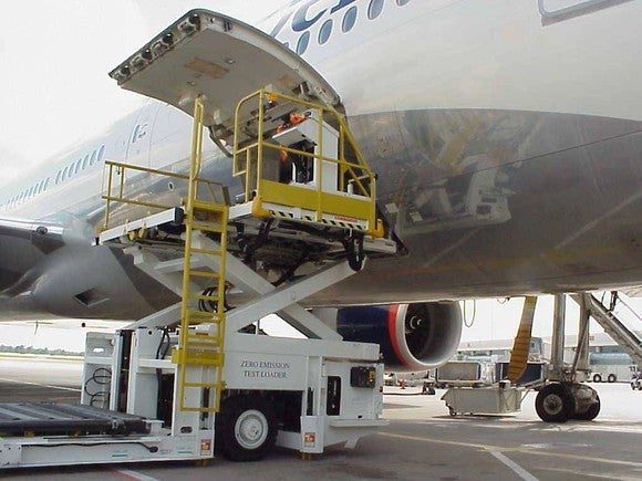 Aircraft loader with its platform raised to the cargo level of a jumbo jet.